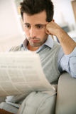 Man reading newspaper at home with sad look a Stock Image