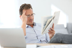 Man reading newspaper at home Stock Photos