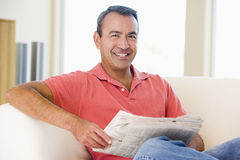 Man reading newspaper in living room smiling royalty free stock photo