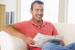 Man reading newspaper in living room smiling royalty free stock images