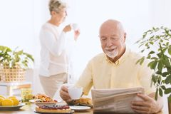 Man reading newspaper. A men reading newspaper during breakfast and his wife drinking coffee behind him stock images