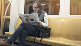 Man reading newspaper in the metro train. Man reading newspaper  in the metro train stock photo