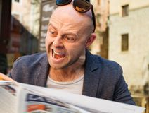 Man reading newspaper. MIddle-aged man becoming enraged while reading newspaper outdoors Royalty Free Stock Photography