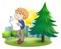 A man reading newspaper near the pine tree Stock Images