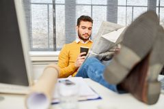 Man reading newspaper at office. During coffee break relaxation royalty free stock photography