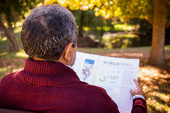 Man reading newspaper while relaxing on bench stock photography