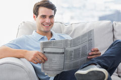 Man reading a newspaper sat on a couch Stock Image