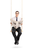 Man reading a newspaper seated on a swing Royalty Free Stock Image