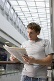 Man Reading Newspaper In Shopping Center. Young men reading newspaper in shopping center Stock Images