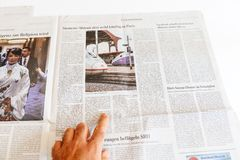 Man reading newspaper about Siemens and Alstom merger. PARIS, FRANCE - SEP 25, 2017: Man reading German newspaper about Siemens and Alstom possible merger Stock Images