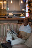 Man reading newspaper while sitting on sofa. In living room at home Stock Images