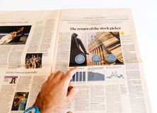 Man reading newspaper about stock markets Financial Times. PARIS, FRANCE - SEP 25, 2017: Man reading international newspaper Financial Times about the return of royalty free stock images
