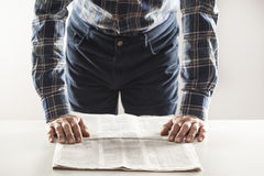 Man reading newspaper on table Stock Photos