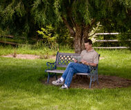 Man reading newspaper under tree. Man sitting on a garden bench reading a newspaper under the shade of a pine tree royalty free stock photography