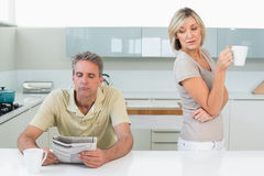 Man reading newspaper and woman with coffee cup Stock Photography