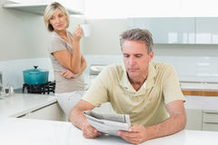 Man reading newspaper while woman at kitchen Royalty Free Stock Photo