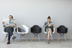 Man reading newspaper and woman using digital tablet. Man reading the newspaper and women using digital tablet Stock Photos