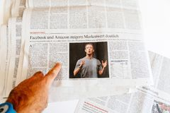 Man reading newspaper Zuckerberg Facebook CEO intention to sell Stock Image