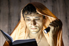 Man reading novel book with flashlight under blanket Royalty Free Stock Photo