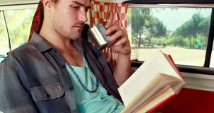 Man reading novel while having coffee in camper van 4k stock video footage