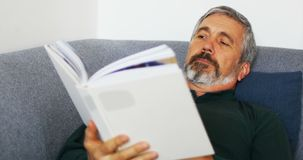 Man reading novel while relaxing on sofa in living room 4k. Man reading novel while relaxing on sofa in living room at home 4k stock footage