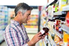 Man reading nutritional values. At supermarket Stock Photos
