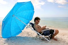 Man Reading by Ocean Under Beach Umbrella Royalty Free Stock Photography