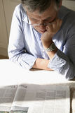 Man reading paper. Senior man with glasses reading a newspaper Royalty Free Stock Image