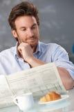 Man reading paper at breakfast Stock Photos