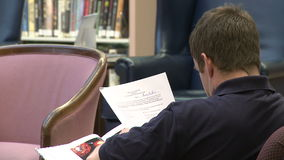 Man reading papers in a library stock video