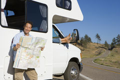 Man reading road map by woman with feet out of window of motor home Royalty Free Stock Images