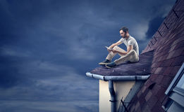 Man reading on a roof Royalty Free Stock Photography