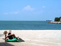 Man reading at seaside. Resort living with sun tanning. A man with suntanned body reading on the beach Stock Image