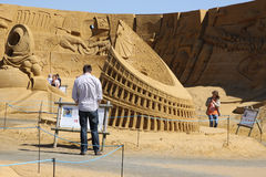 Man reading sign at sand sculpture festival Royalty Free Stock Image
