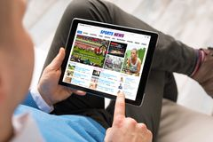 Man reading sports news on tablet. All contents are made up. stock photo