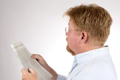Man Reading Stock Market Report. Mature male reads the stock market report in the newspaper to glean financial information and improve his investments Royalty Free Stock Image