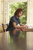 Man Reading At Table By Window Stock Photography