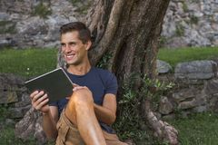 Man reading tablet and enjoy rest in a park under tree stock image