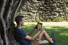 Man reading tablet and enjoy rest in a park under tree royalty free stock photos