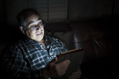 Man reading tablet at night Stock Images