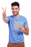 Man reading on tablet pad and making the victory sign Stock Image