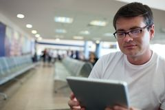 Man reading on tablet PC while waiting at the Royalty Free Stock Images