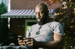 Man Reading Text Message in Garden. African American man reacts as he reads and email or text message while enjoying a glass for red wine in the backyard garden royalty free stock photography