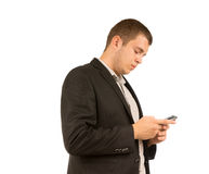 Man reading a text message on his mobile phone. Young man in a stylish jacket standing reading a text message on his mobile phone with a serious expression in a Royalty Free Stock Image