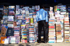 Man reading the titles of books. On the photo: Man reading the titles of books in the street booksellers in Mumbai Royalty Free Stock Photography