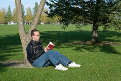 Man Reading By A Tree. A young man resting by a tree and reading a book Royalty Free Stock Photo