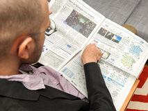 Man reading tv programmes and tv schedules for the upcoming week Stock Photography