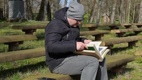 Man reading two books on bench in park stock footage