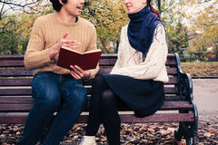 Man reading for woman on park bench Stock Photo