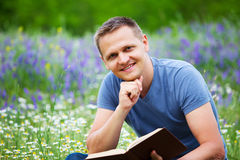 A man reads a book in the field. Royalty Free Stock Image